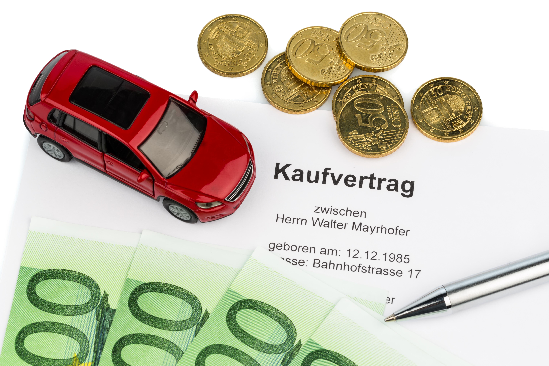 Ein Kaufvertrag für einen Autokauf beim Autohändler. Neu- und Gebrauchtwagen